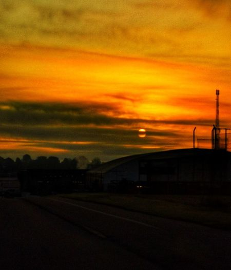 Road by silhouette city against orange sky