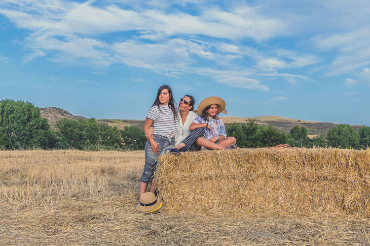 Mother And Daughter With Hay Bale On Landscape Against Blue Sky