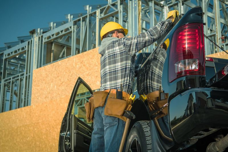 Construction Industry Business. Caucasian Contractor Worker in Front of the Newly Built Structure Looking For Tools Inside His Pickup Truck. Pickup Truck Construction Worker Work Job Builder Labor Men Transportation Vehicle Car Skeleton Structure Home House Developer