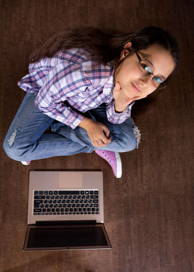 High angle portrait of girl sitting by laptop at home
