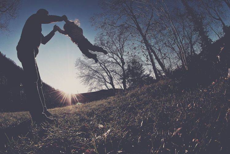 Low angle view of father swinging daughter at dusk