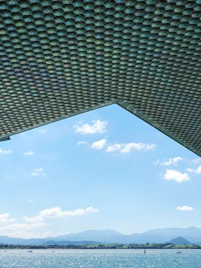 Low Angle View Of Patterned Ceiling By Sea Against Blue Sky