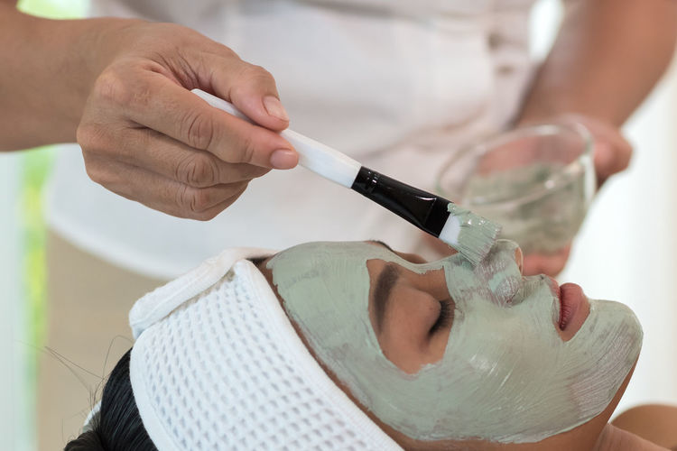 Midsection of beautician applying facial mask on woman face at spa