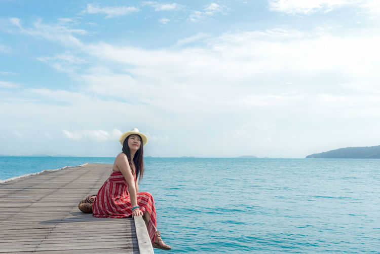 Full length of young woman in sea against sky