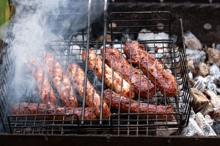 Appetizing crisp pork sausages on barbecue grill with smoke. summer outdoor picnic.