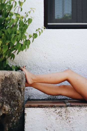 Low section of woman relaxing on wall