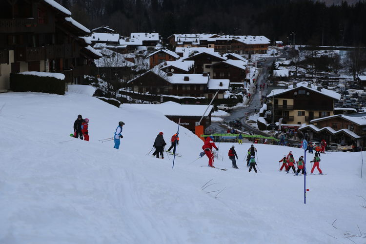 People skiing on snow covered field by houses