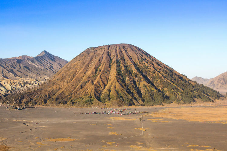 Layer Volcanic ash as sand ground of Mount Bromo volcano the magnificent view of Mt. Bromo located in Bromo Tengger Semeru National Park, East Java, Indonesia. Beauty In Nature Blue Calm Clear Sky Day Geology In Front Of Majestic Mountain Mountain Peak Mountain Range Natural Landmark Nature No People Non-urban Scene Outdoors Physical Geography Remote Scenics Solitude Tranquil Scene Tranquility View Into Land Water Waterfront