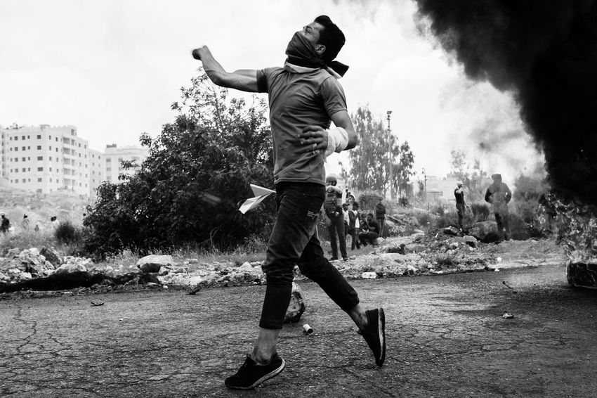 Palestinian using a slinger to throw rocks at Israeli soldiers in Ramallah during clashes for Nakba day commemoration, on the 15th of May in Palestine. Middle East The Photojournalist - 2018 EyeEm Awards Architecture Built Structure Casual Clothing Day Documentary Full Length Incidental People Journalism Leisure Activity Lifestyles Men Motion Nature One Person Outdoors Park Plant Real People Rear View Reportage Sport Tree