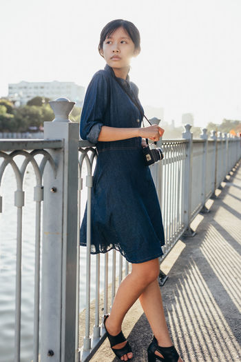 Portrait of woman standing on railing against bridge