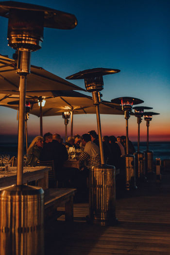 Male and female friends sitting by table at beach during sunset