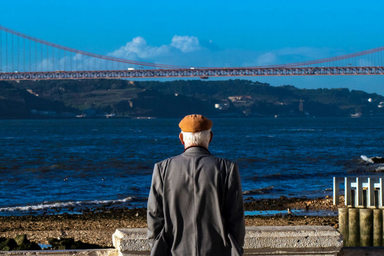Rear view of man standing against bridge and sea