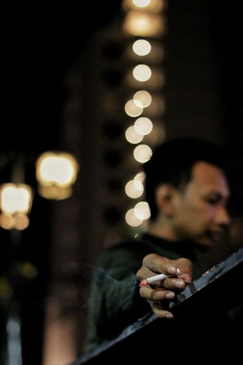 Side View Of Young Man Holding Cigarette Against Defocused Lights At Night