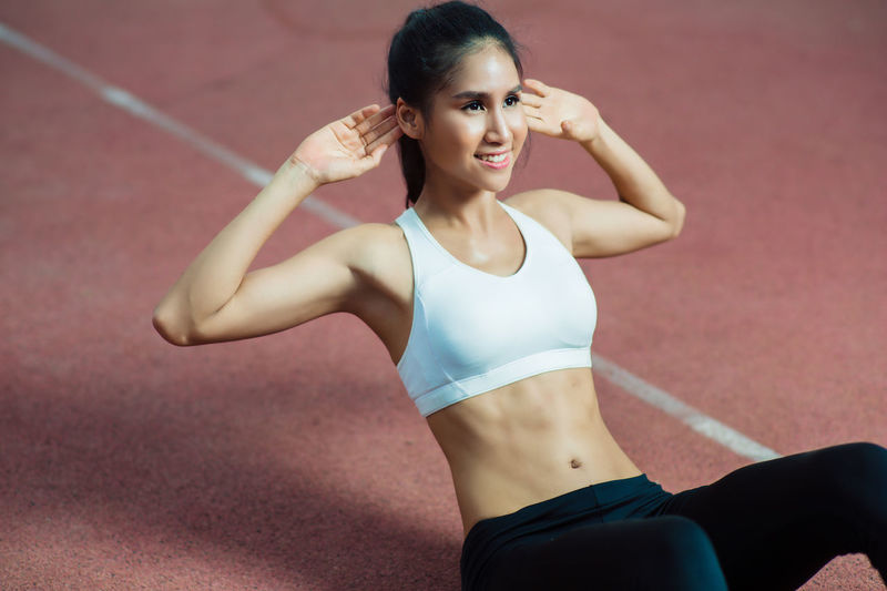 Arms Raised Athlete Beautiful Woman Beauty Clothing Exercising Front View Healthy Lifestyle Human Arm Lifestyles One Person Portrait Real People Shorts Sport Sports Bra Sports Clothing Standing Strength Three Quarter Length Women Young Adult Young Women