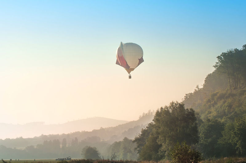 A hot air balloon starts its flight. it's early morning, the fog is above nature. unusual shape.