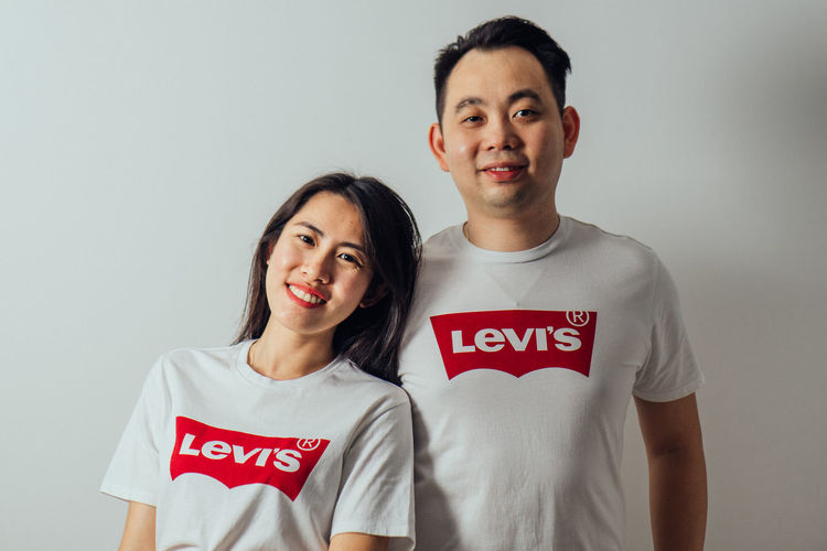 Looking At Camera Portrait Front View Smiling Text Standing Casual Clothing Indoors  Western Script Two People Emotion Waist Up Happiness Young Men Young Adult Real People People Men Lifestyles Positive Emotion Levis LEVIS™ Couple Love