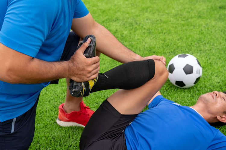 Low Section Of Male Physical Therapist Stretching Soccer Player Leg On Field