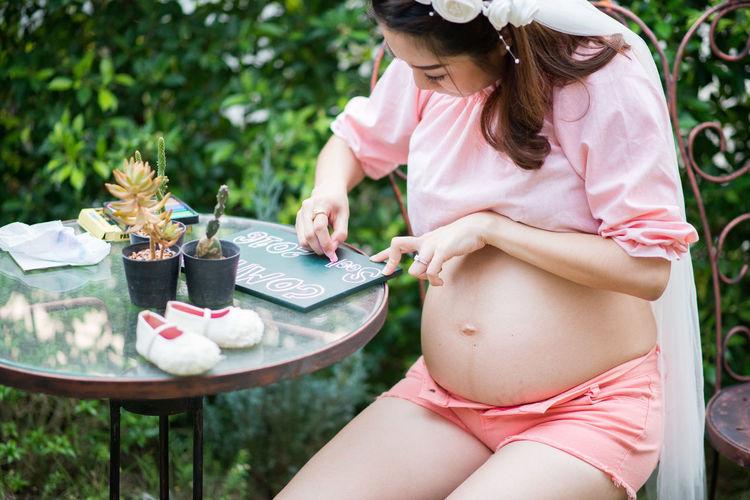 Pregnant woman sitting in yard