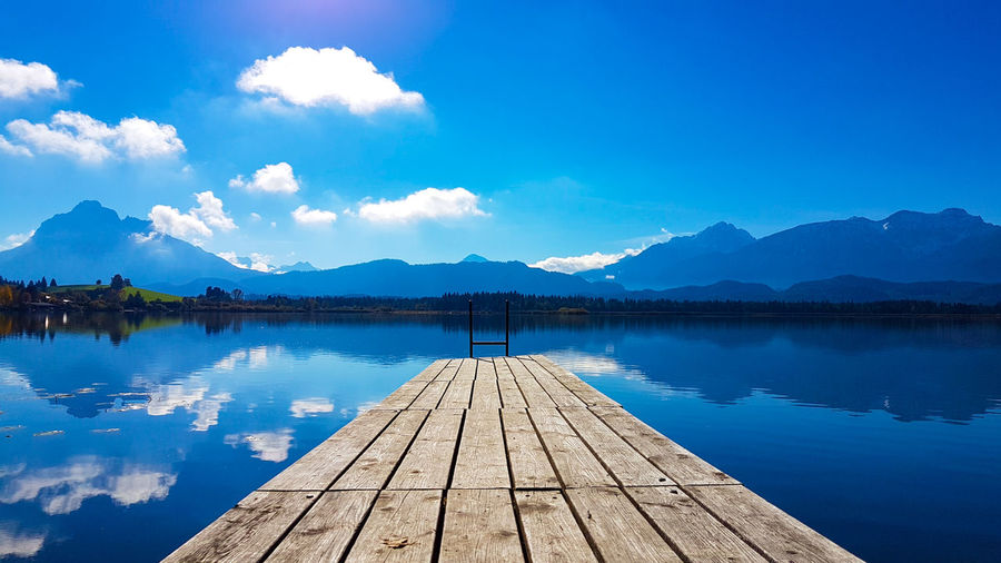 Lake Water Reflection Blue Landscape Mountain Nature Pier Sky Scenics Nautical Vessel Travel Arrival Horizontal Travel Destinations Outdoors Mountain Range Silence Tranquil Scene Beauty In Nature First Eyeem Photo Freshness Outdoor Pursuit Floating On Water No People