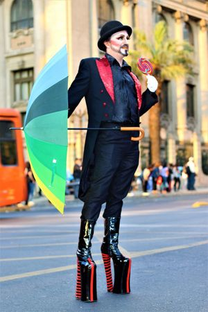 Uniqueness Rebelde Drag Black Man Hi Shoes Rainbow Umbrella Black Hat Day Adult City Street Communication Actor Showing His Character Performance At The Street