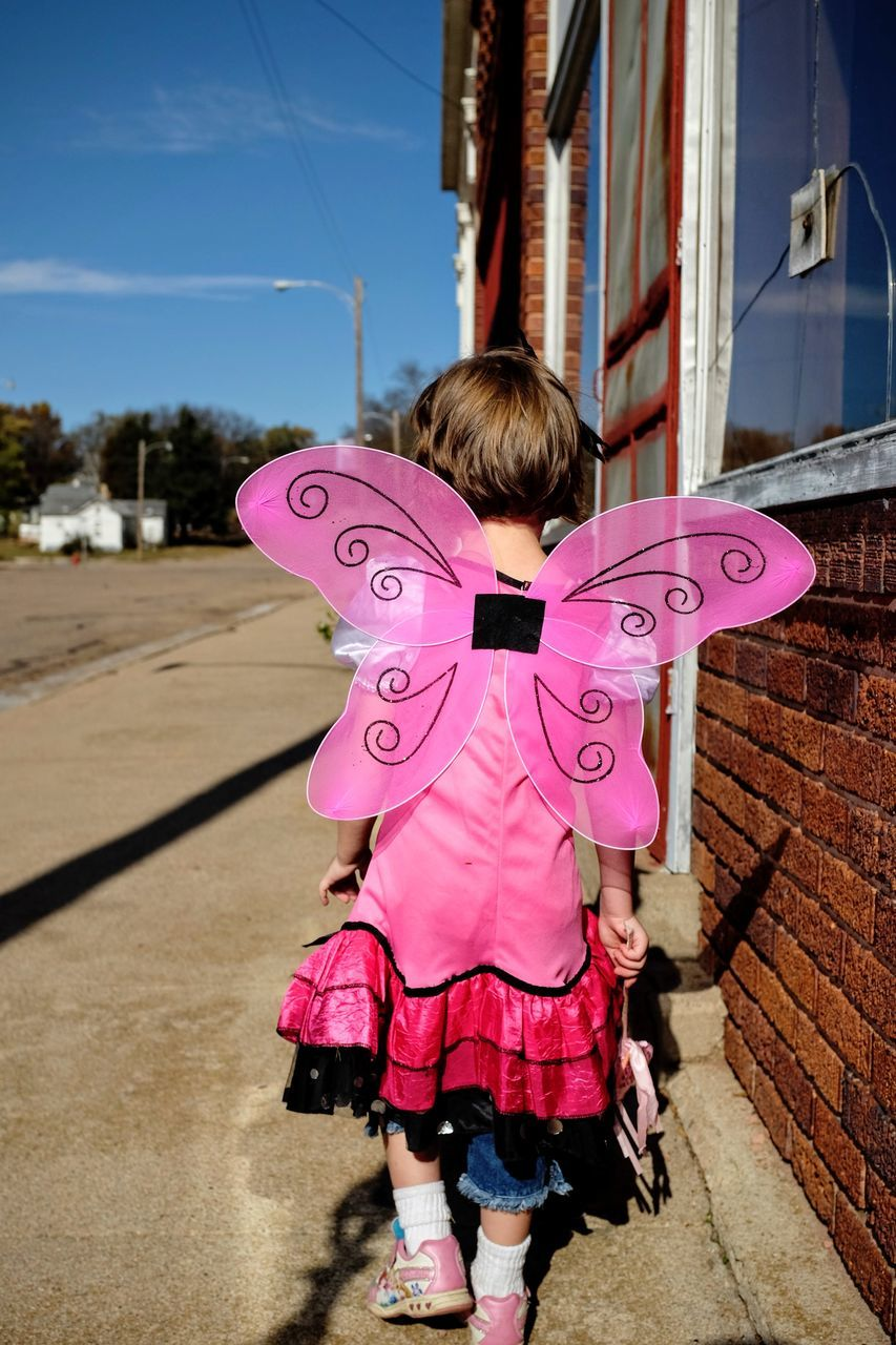 Rear View Of Girl Wearing Pink Wings While Walking On Footpath By Building In City