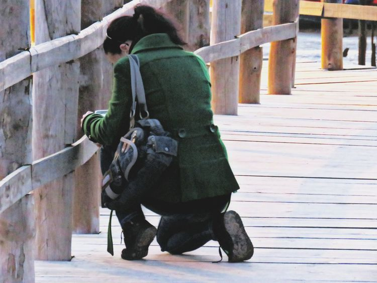Selective Focus Woman Kneeling Down Taking Pictures Wood Pier Pier Wood Single Person Serenity Focus Ponytail Walking Around Check This Out EyeEm Best Shots Eye4photography  One Person Distracted Caught Off Guard Kneeling Women Who Inspire You Woman's Purse Purse Green Coat Focused Girl With Green Jacket