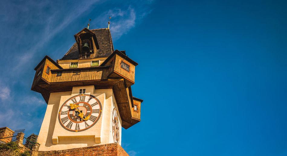 uhrturm landmark in graz cityscape view, styria region of austria. clocktower against blue sky