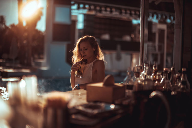Young woman having drink at restaurant