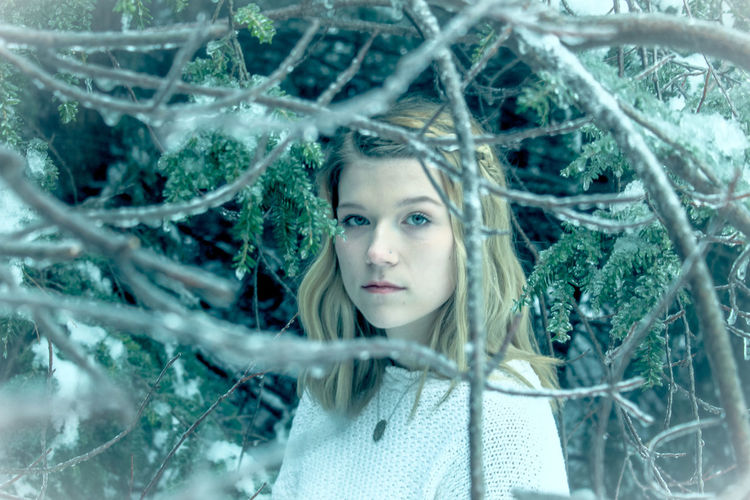 Portrait of teenage girl standing amidst frozen tree branches in forest