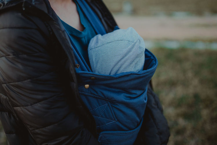 Rear view of woman with baby in carrier in park