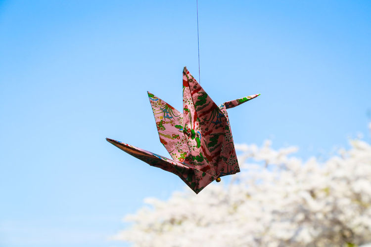 Close-up of paper crane hanging from string against clear blue sky