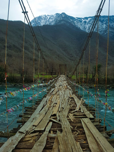 Old bridge Nobody Bridge Suspension Mountain Turquoise Spring Wood Board Forest Road Trees Water Sky Empty Road