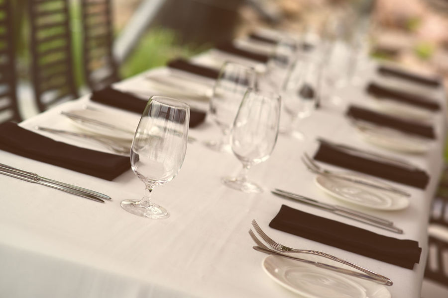Table setting. Glasses and plates on table in a restaurant Celebration Close-up Decoration Event Fork Glasses Glassware Holiday Marriage  Matrimony Napkins No People Nobody Party Plate Plates Reataurant Restaurant Served Table Table Arrangements Table Setting Wedding White And Black Wineglasses