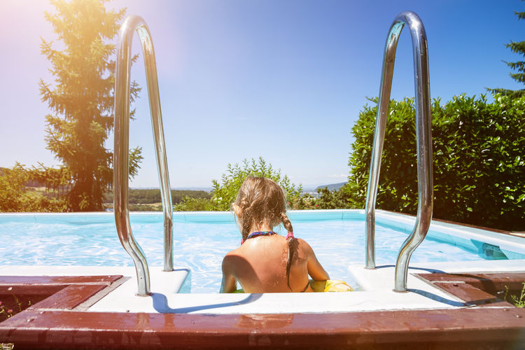Rear view of woman sitting by swimming pool against sky