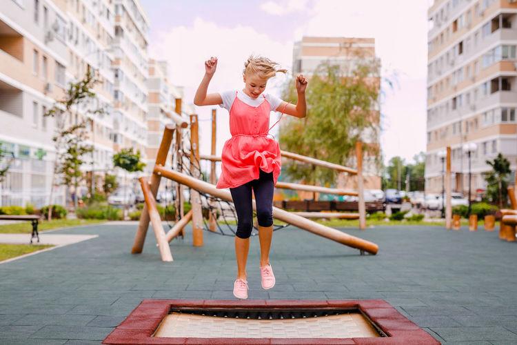 Full length of girl jumping on trampoline