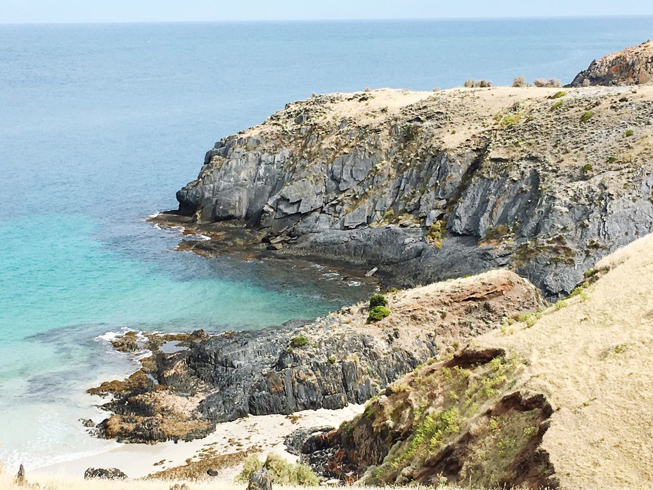 sea, rock - object, nature, rock formation, beauty in nature, scenics, water, tranquility, tranquil scene, rock, cliff, day, horizon over water, sunlight, no people, outdoors, physical geography, sky, blue, beach