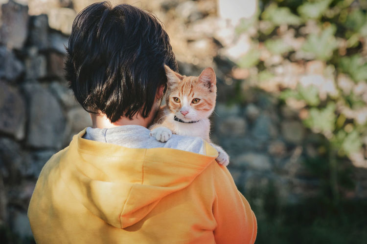 Rear view of boy holding cat outdoors
