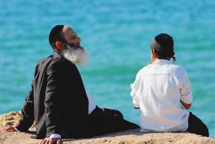 Adult Beauty In Nature Israel Judaism Lifestyles Nature People Rabbinical Rear View Religion Sea Sitting Tel Aviv Beach Two People Water