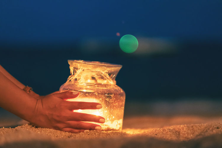 Close-up of woman hand holding illuminated lighting equipment in glass jar at beach during night