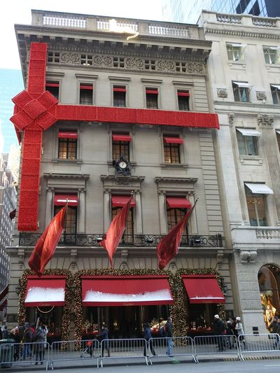 Cartier Building Exterior Architecture Built Structure Façade Christmas Decoration Oversized Bow Christmas Lights Snow Dusted Canopies Flags Waving People NYC Christmas Photography