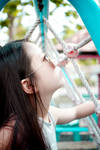 Close-up side view of cute girl by ropes in playground
