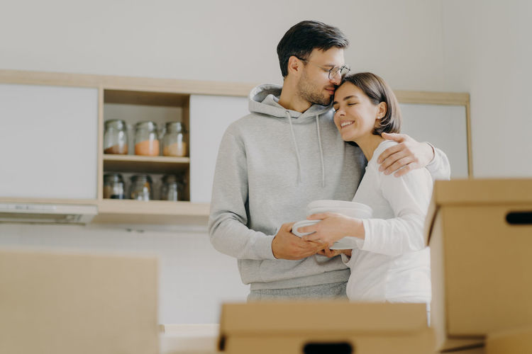 Low angle view of couple embracing while standing at home