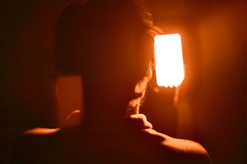 Close-up portrait of silhouette woman against illuminated light
