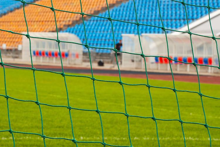 Close-up of soccer field seen through goal post net