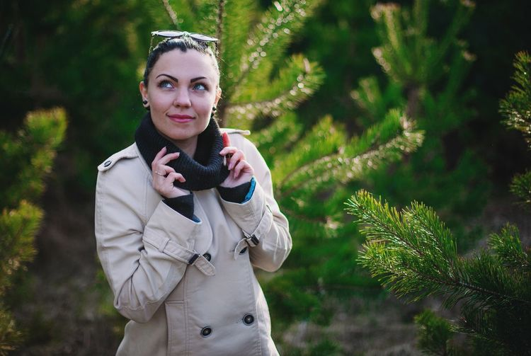 Young woman wearing winter coat looking up while standing against plants