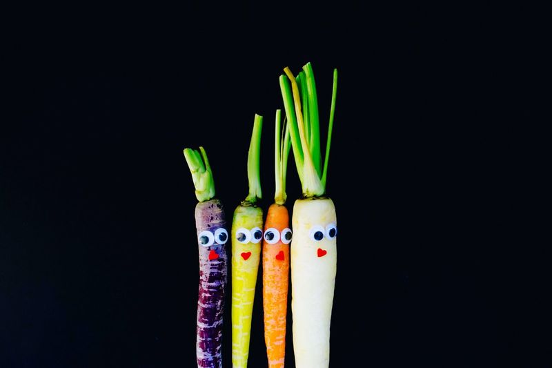 Close-up of colorful carrots with googly eyes against black background