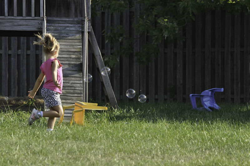 Young Girl Playing with Bubbles Young Bubble Childhood Front Or Back Yard Full Length Girl Leisure Activity One Person Outdoors Park People Playing Real People Spring Summer