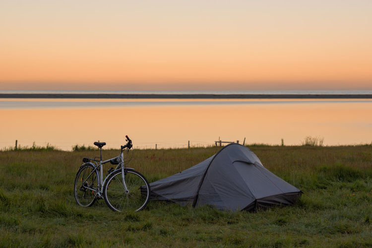 Bicycle on grassy field at campsite by lake against clear sky during sunset