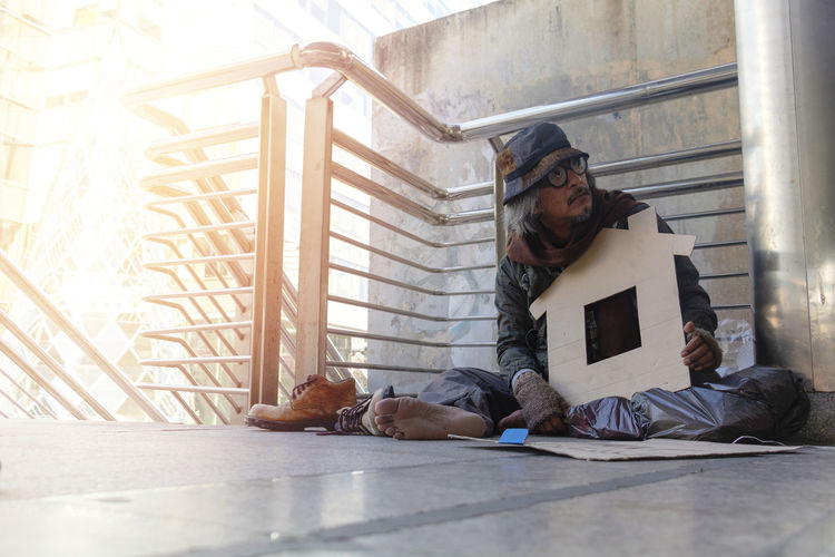 Full length of homeless person sitting on footpath