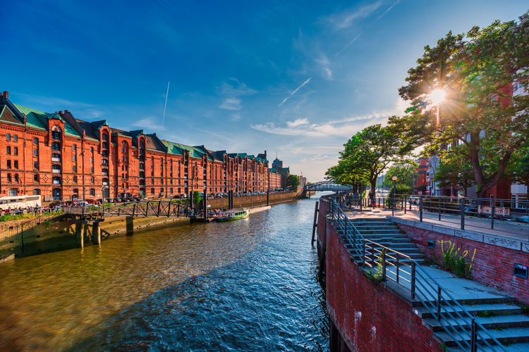 Panoramic view of canal amidst buildings in city against sky